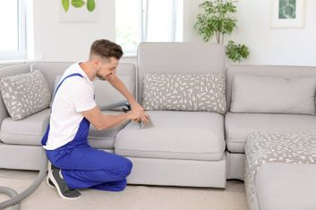 man cleaning sofa